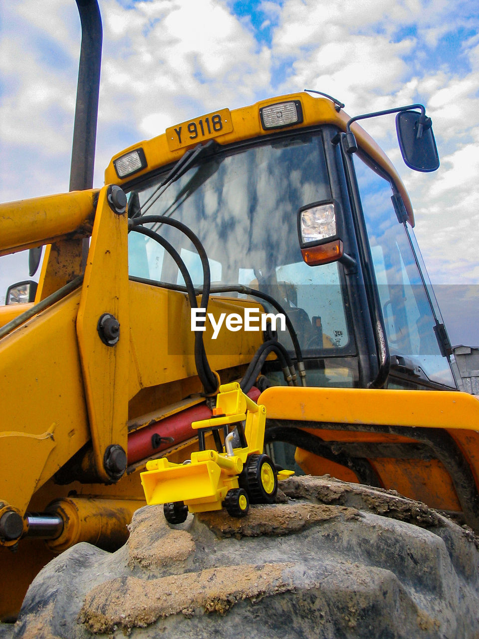 yellow, construction machinery, land vehicle, mode of transportation, earth mover, transportation, construction industry, bulldozer, construction site, day, construction vehicle, machinery, nature, cloud - sky, sky, outdoors, industry, no people, road construction, commercial land vehicle, construction equipment, school bus, junkyard, industrial equipment