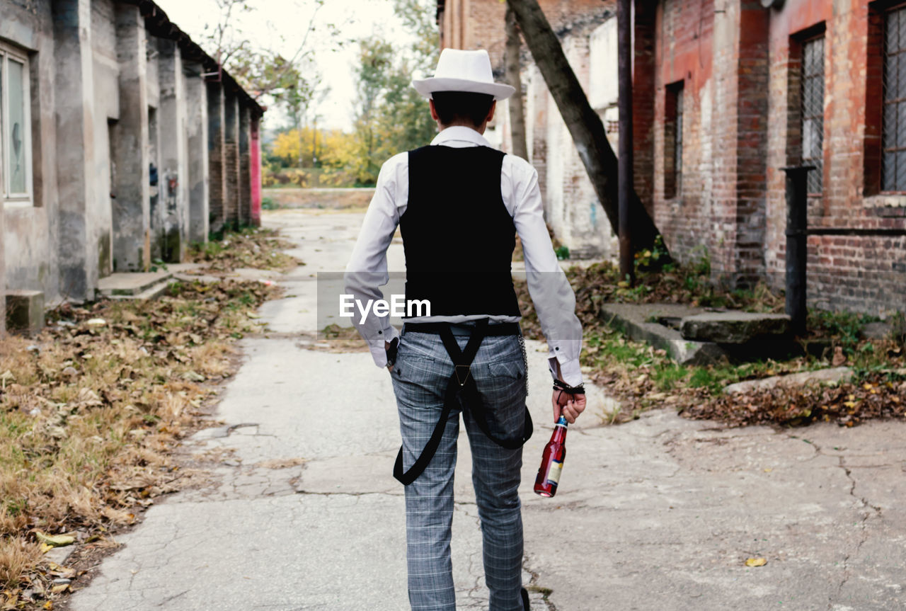 Rear view of retro-styled man carrying beer bottle while walking on the street.