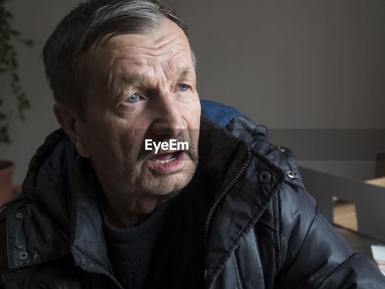 Close-up of senior man looking away at home