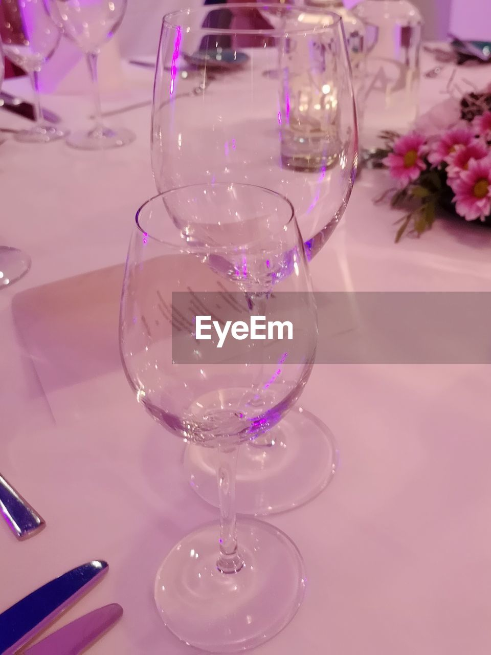 glass, table, household equipment, transparent, indoors, glass - material, no people, wineglass, drinking glass, food and drink, refreshment, vulnerability, flower, freshness, still life, fragility, drink, flowering plant, nature, pink color, setting, luxury, flower arrangement