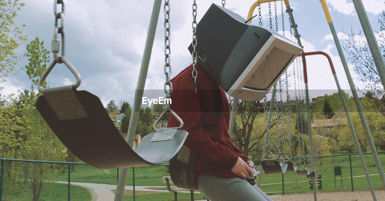 Man wearing television set while sitting on swing at playground