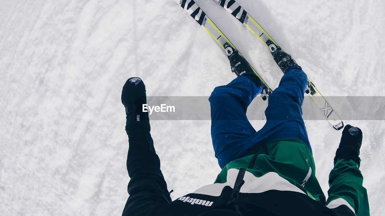 real people, men, day, one person, winter, cold temperature, low angle view, snow, lifestyles, sport, leisure activity, winter sport, nature, arms raised, low section, clothing, outdoors, skiing, human arm, warm clothing