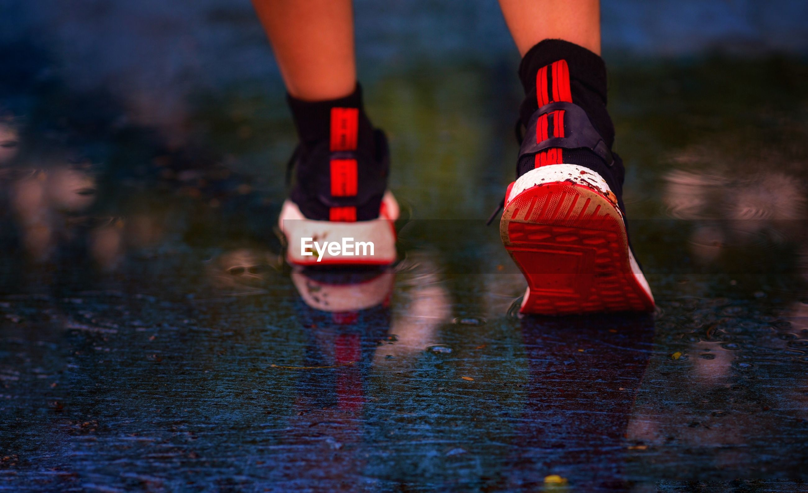 Low section of person wearing red shoes walking on wet road