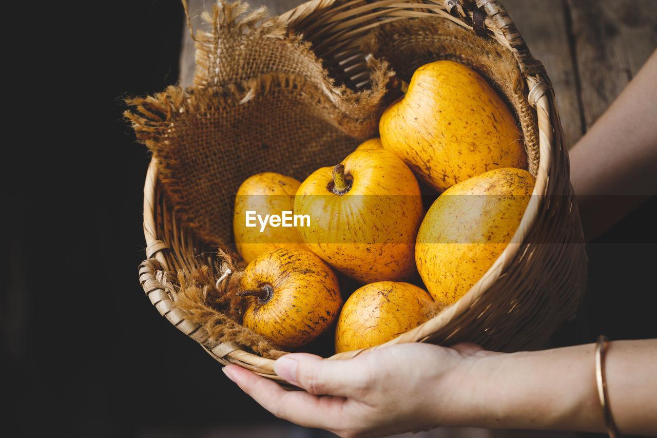 Close-Up Of Man Holding Pumpkin In Basket