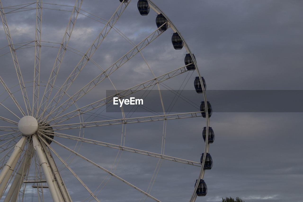 amusement park ride, amusement park, ferris wheel, sky, cloud - sky, arts culture and entertainment, low angle view, nature, no people, leisure activity, day, fairground, outdoors, geometric shape, circle, architecture, built structure, large, shape, spinning, wheel, spoke