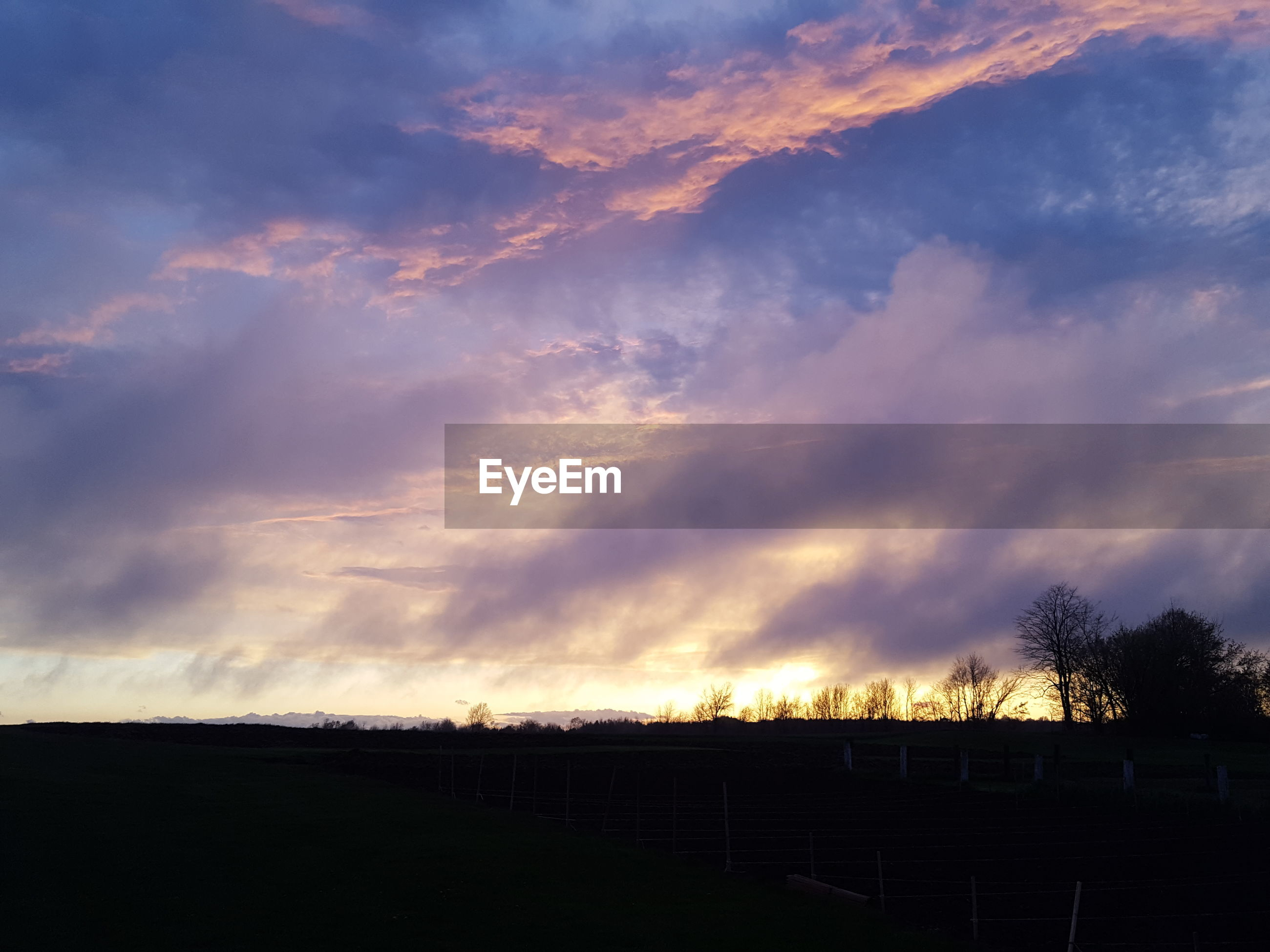 SCENIC VIEW OF LANDSCAPE AGAINST CLOUDY SKY AT SUNSET
