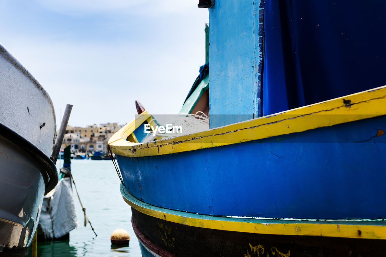transportation, nautical vessel, mode of transportation, day, water, sky, no people, nature, moored, metal, yellow, outdoors, blue, focus on foreground, architecture, ship, container ship, close-up, built structure, fishing boat, wheel, rowboat