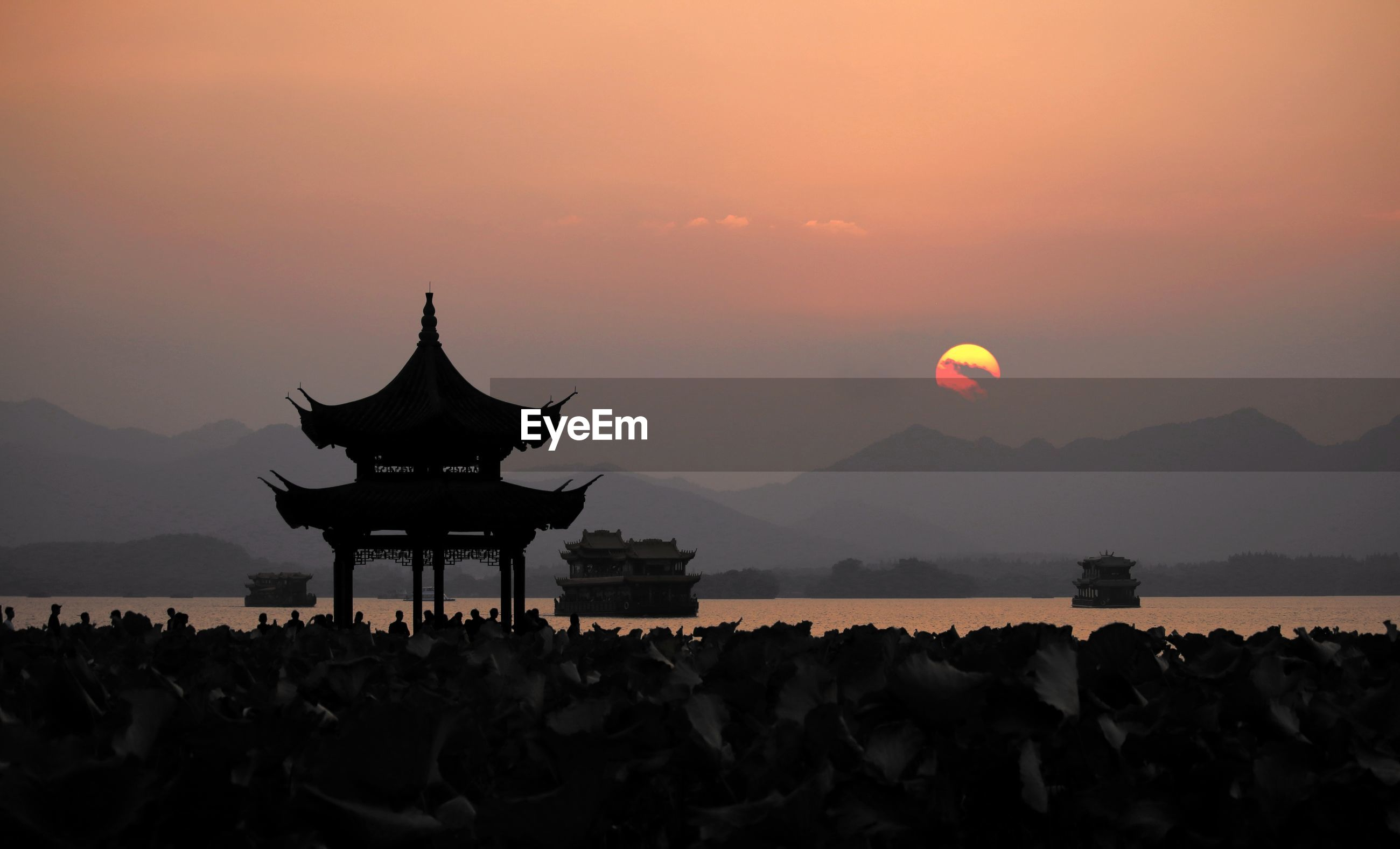 Silhouette pagoda by sea against sky during sunset