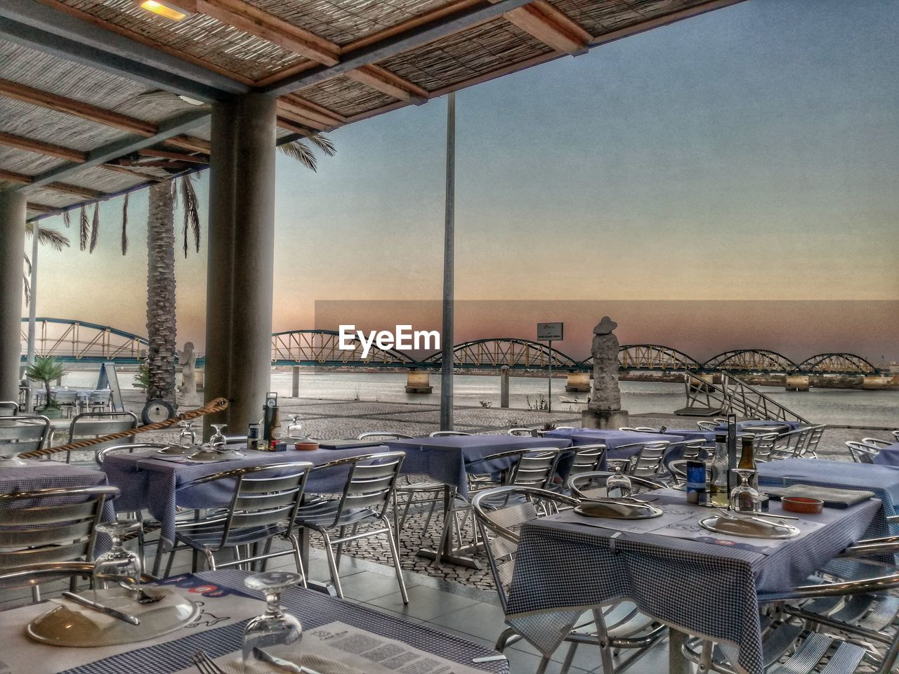 table, chair, outdoor cafe, place setting, absence, empty, restaurant, clear sky, sea, no people, day, architecture, group of objects, outdoors, sky, built structure, beach, water