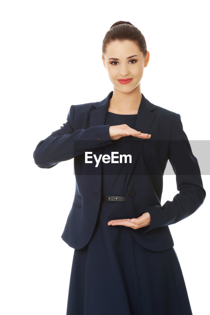 Young businesswoman standing against white background