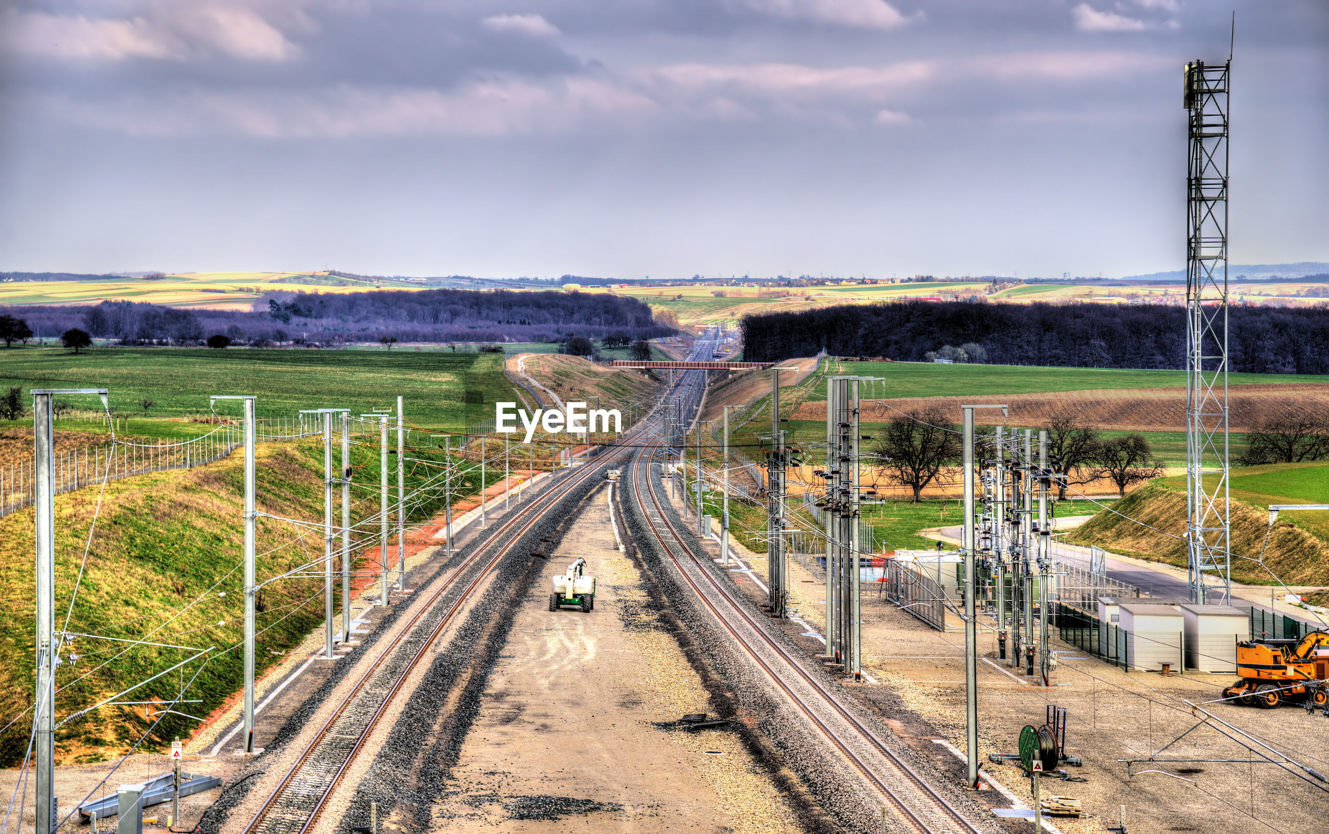 HIGH ANGLE VIEW OF RAILROAD TRACKS AMIDST LANDSCAPE AGAINST SKY