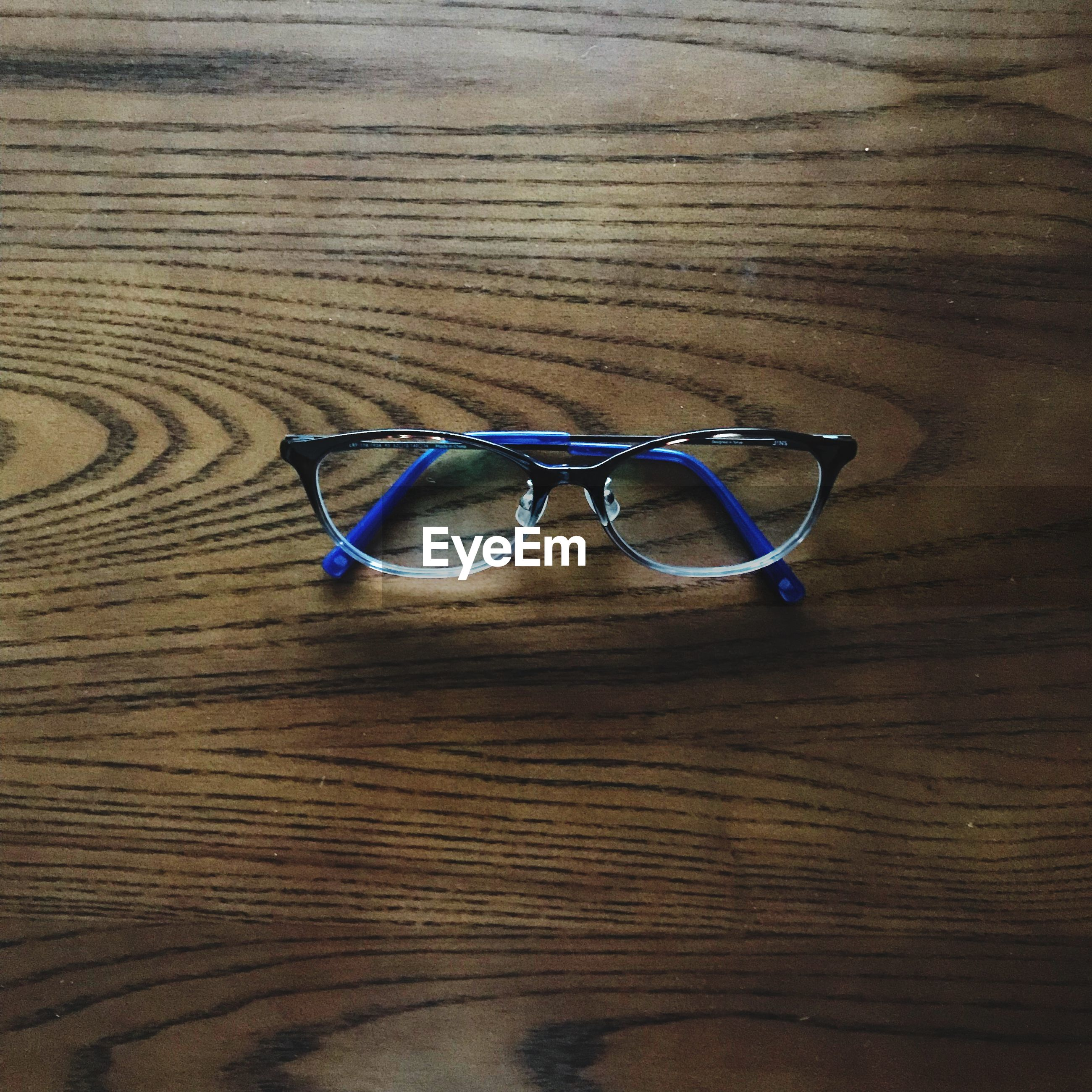 glasses, table, still life, eyeglasses, wood - material, indoors, close-up, no people, personal accessory, single object, high angle view, eyesight, wood, transparent, two objects, sunglasses, eyewear, vision, brown, flooring, wood grain