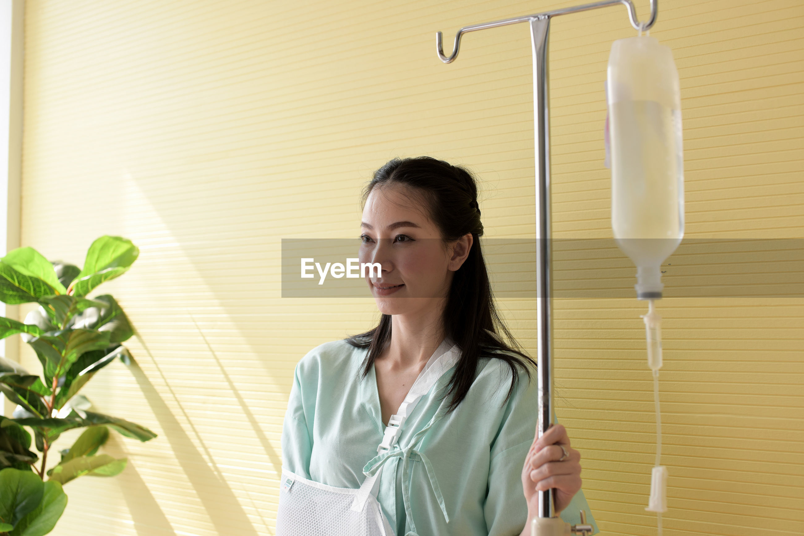 Smiling woman with iv drip standing against wall