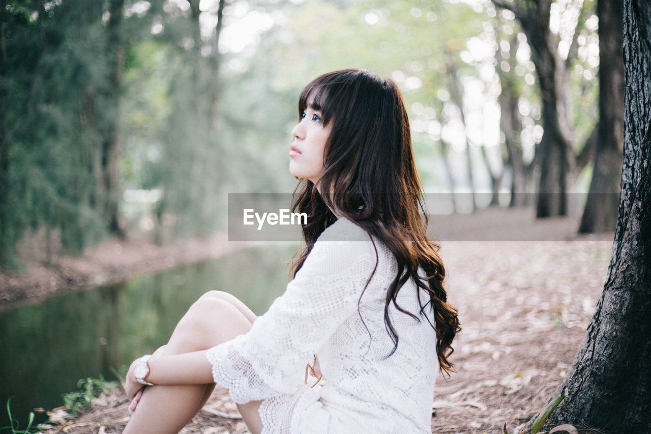 Side View Of Thoughtful Young Woman Sitting At Stream In Forest