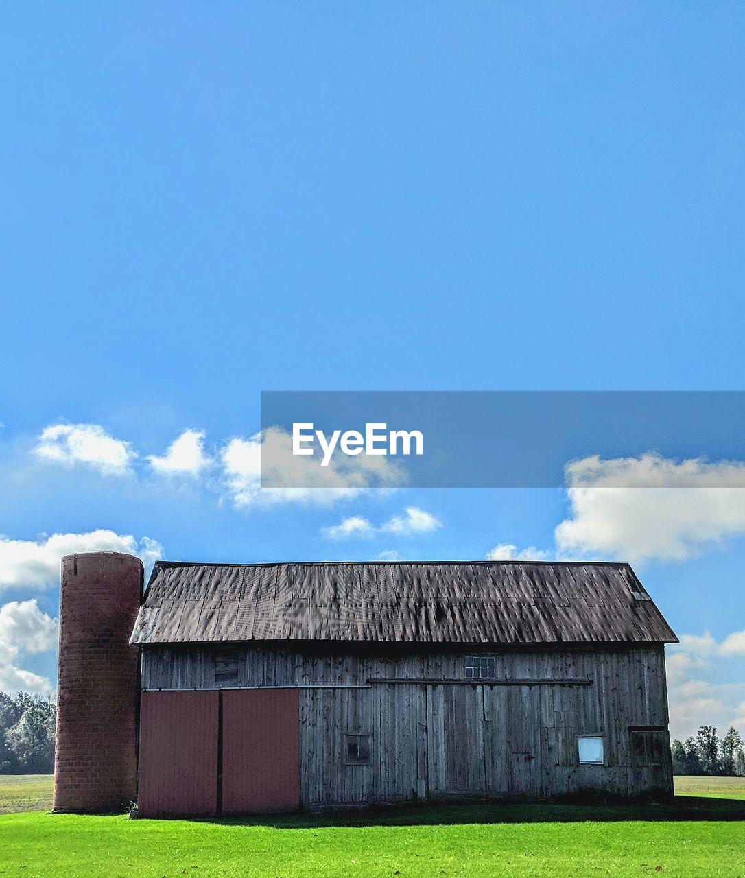 HOUSE ON FIELD AGAINST BLUE SKY