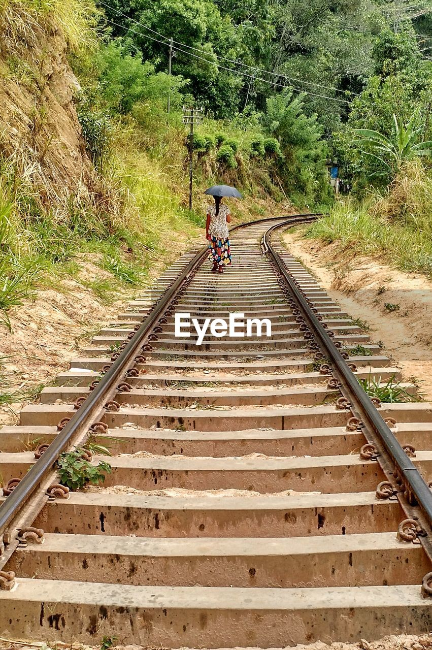 transportation, rail transportation, track, railroad track, the way forward, direction, mode of transportation, plant, tree, day, land vehicle, real people, men, bicycle, lifestyles, nature, ride, riding, people, diminishing perspective, outdoors