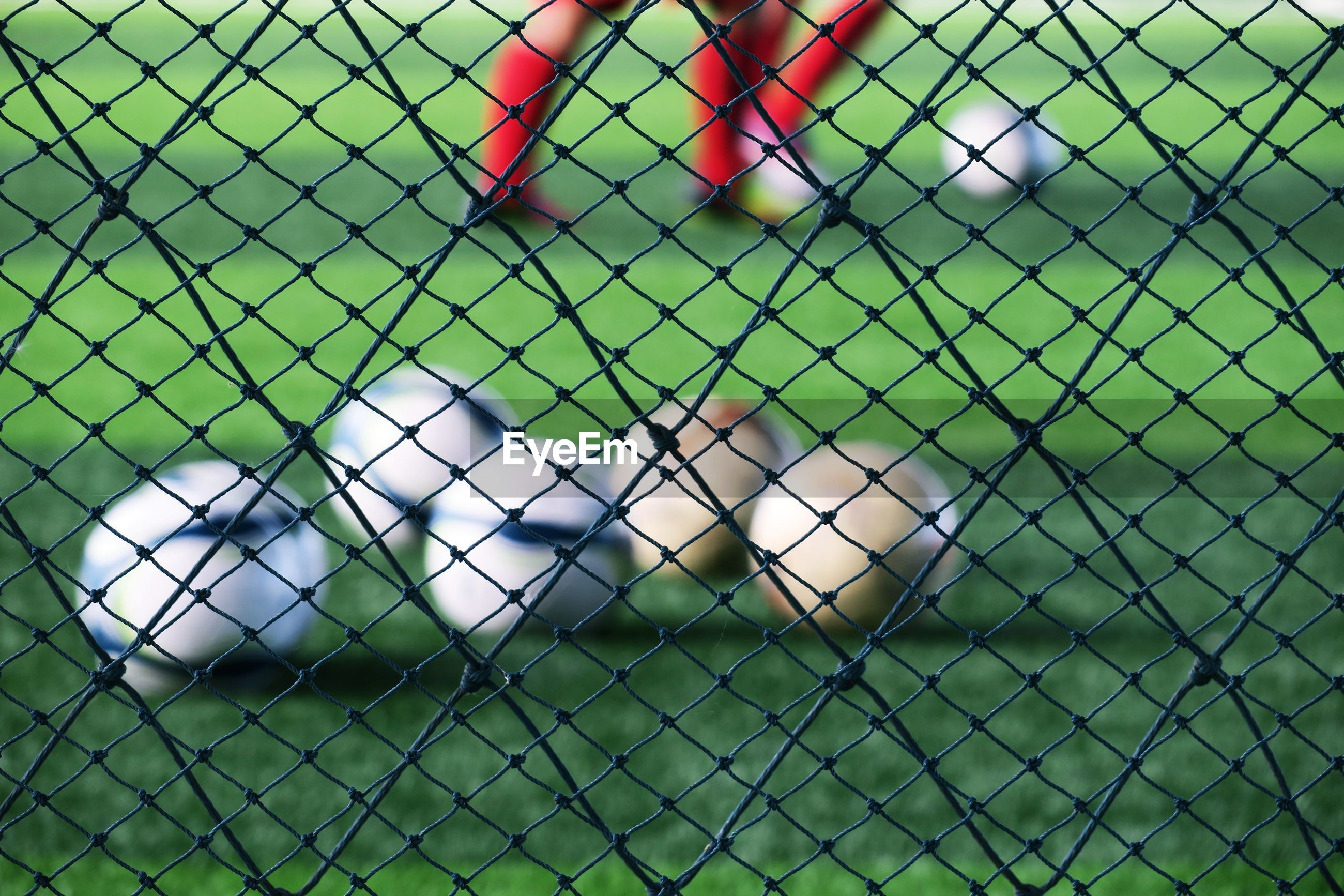 Low section of soccer players playing on field seen through net