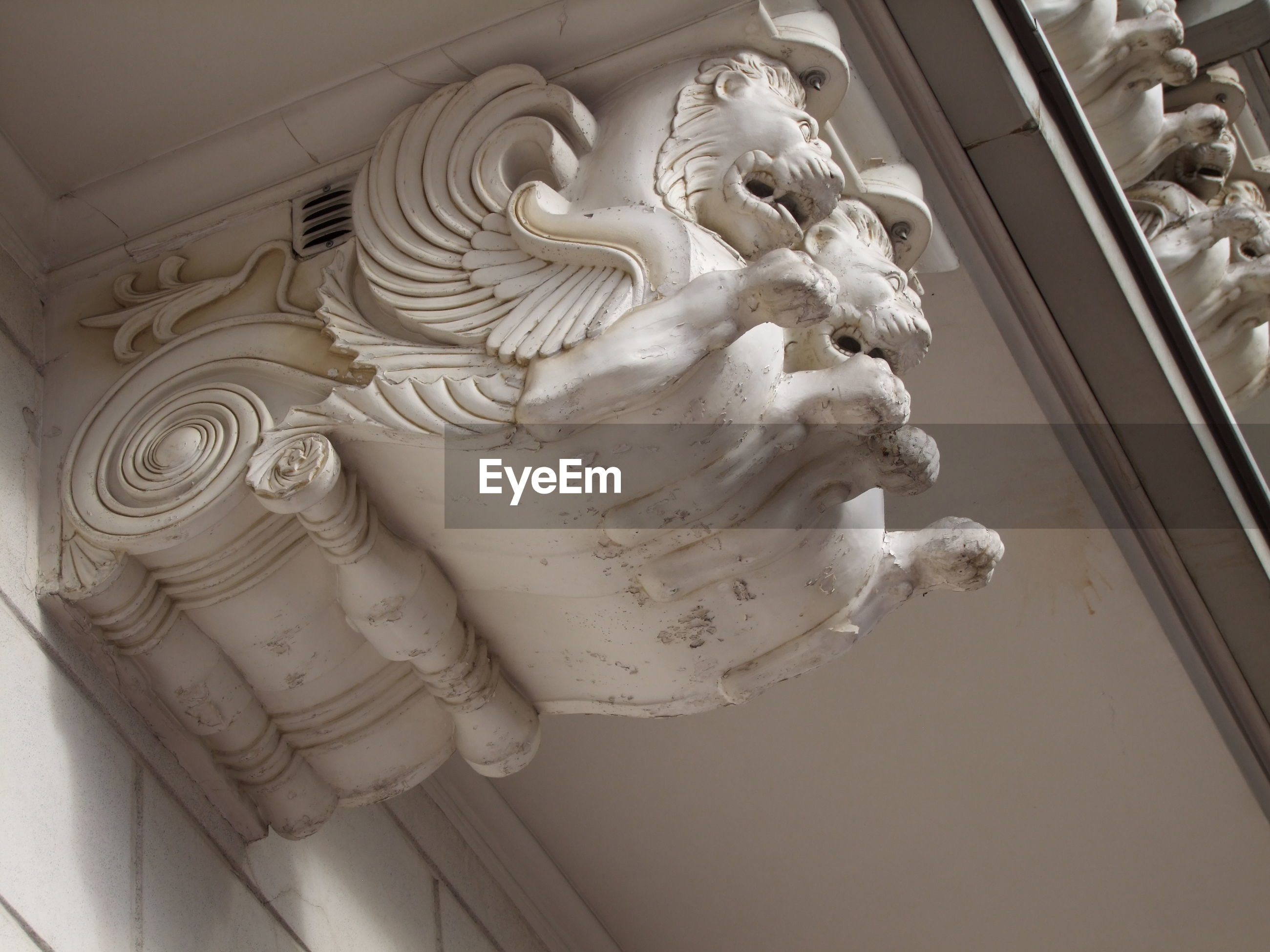 Low angle view of lion sculpture on wall of historic building