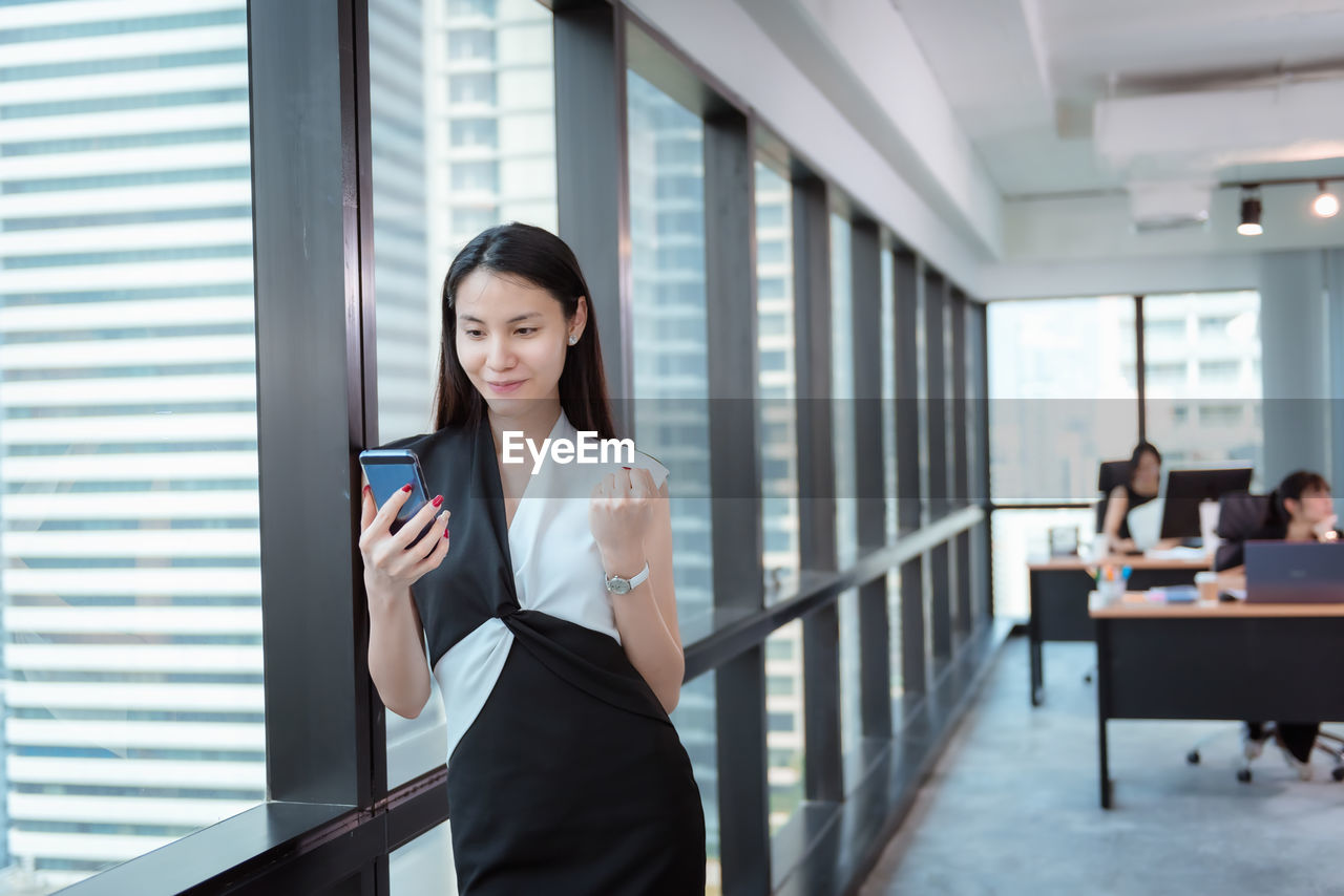 business person, wireless technology, communication, technology, women, businesswoman, young adult, mobile phone, business, adult, office, connection, smart phone, portable information device, holding, young women, one person, real people, indoors, front view