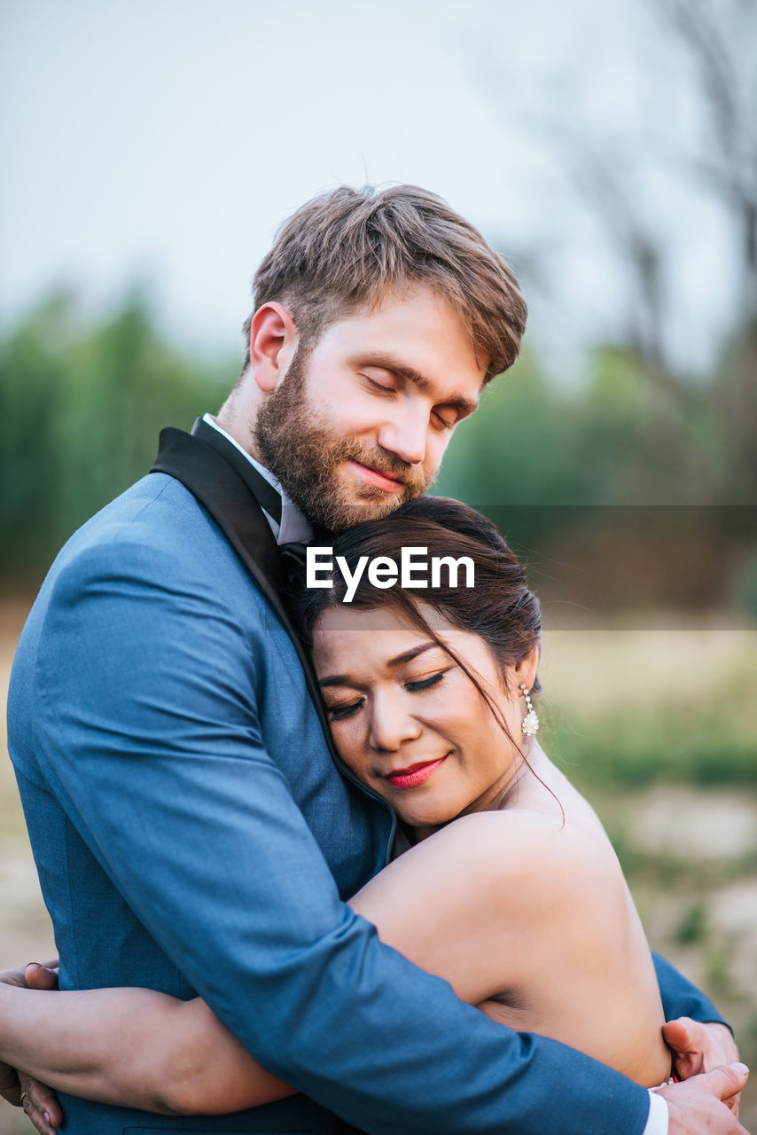Smiling newlywed couple embracing with eyes closed