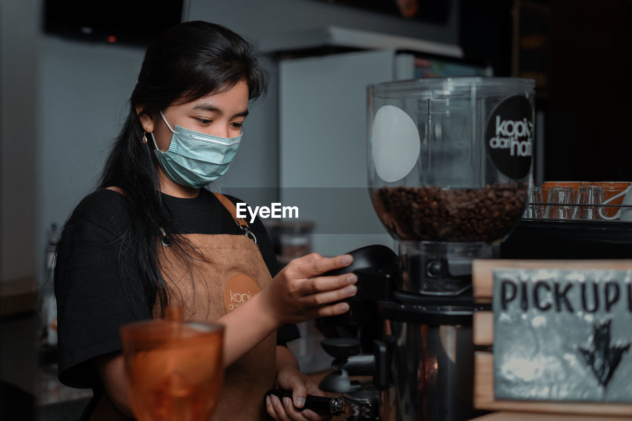 YOUNG WOMAN WORKING AT CAFE