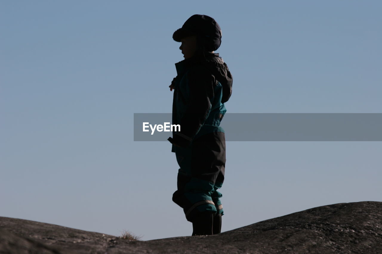 Boy standing on rock against clear sky