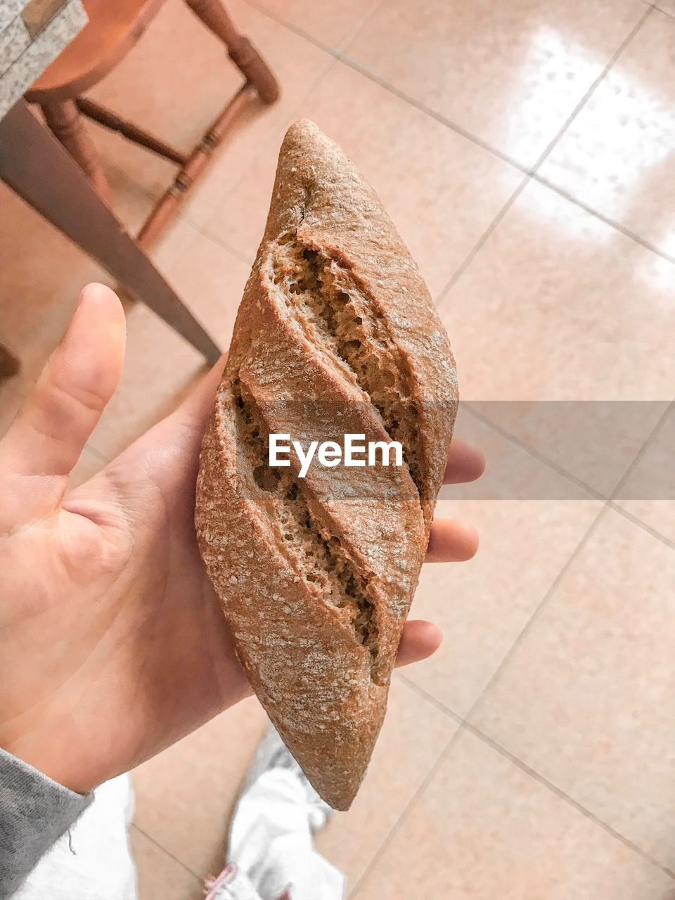 human hand, hand, one person, human body part, bread, holding, food, high angle view, food and drink, real people, freshness, tile, indoors, lifestyles, flooring, close-up, personal perspective, body part, tiled floor, finger, snack