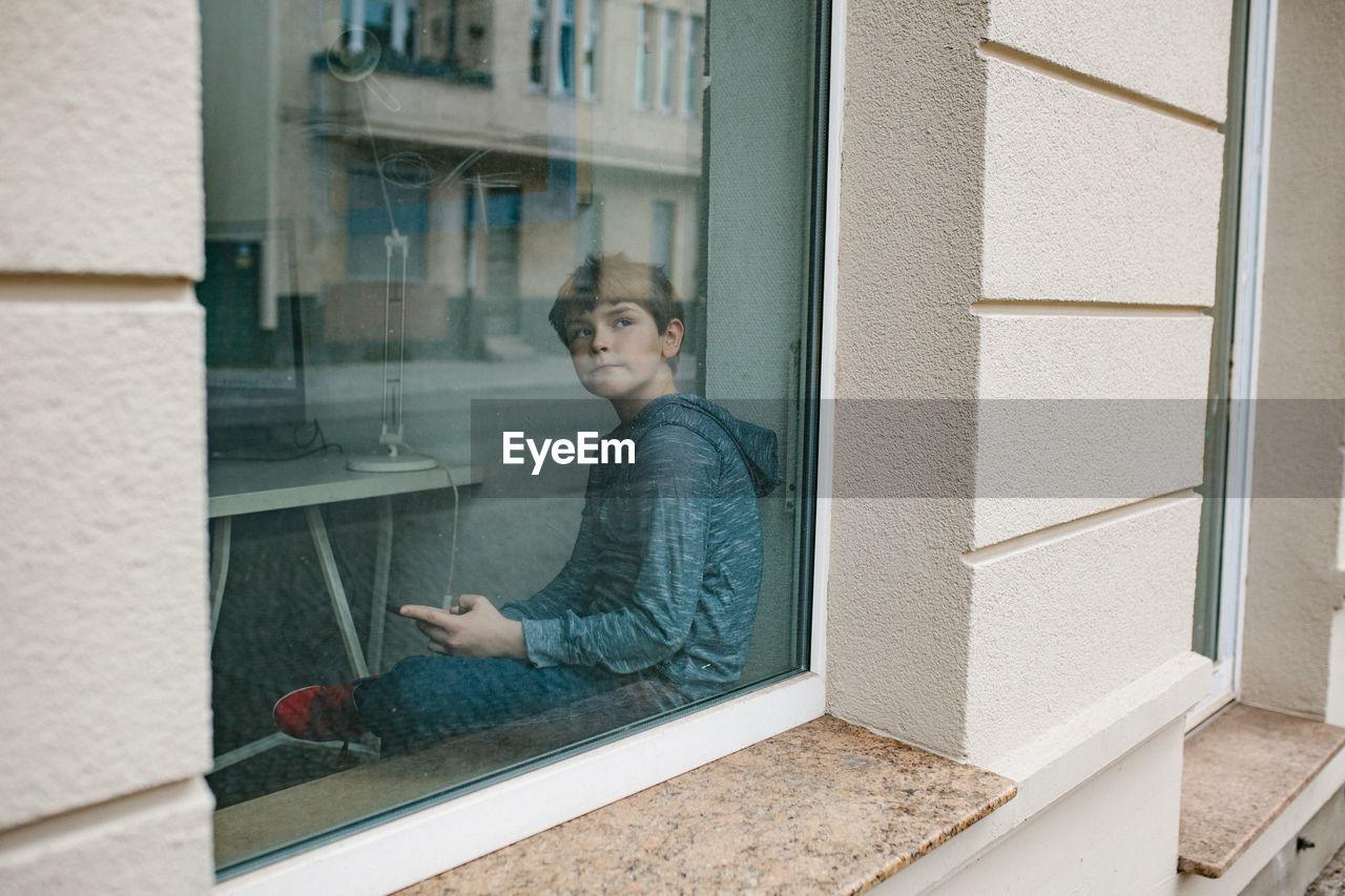 Thoughtful boy sitting by window