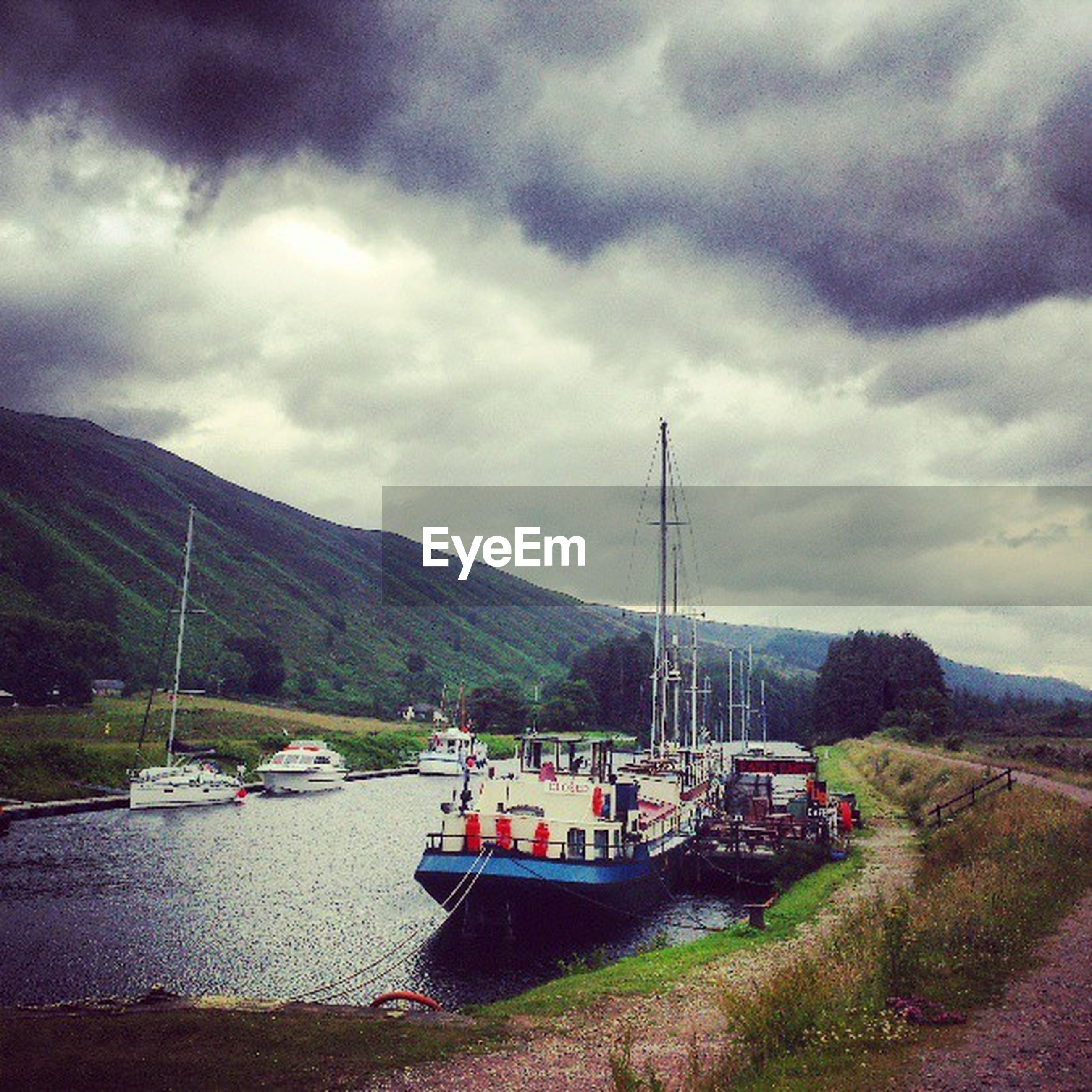 mountain, transportation, sky, nautical vessel, cloud - sky, cloudy, mode of transport, boat, water, mountain range, tranquility, tranquil scene, moored, cloud, scenics, beauty in nature, nature, river, lake, overcast