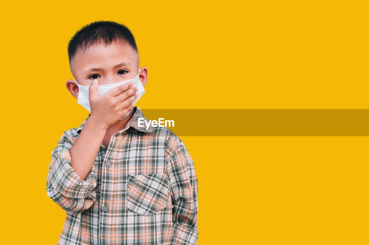 Portrait of boy standing against yellow background