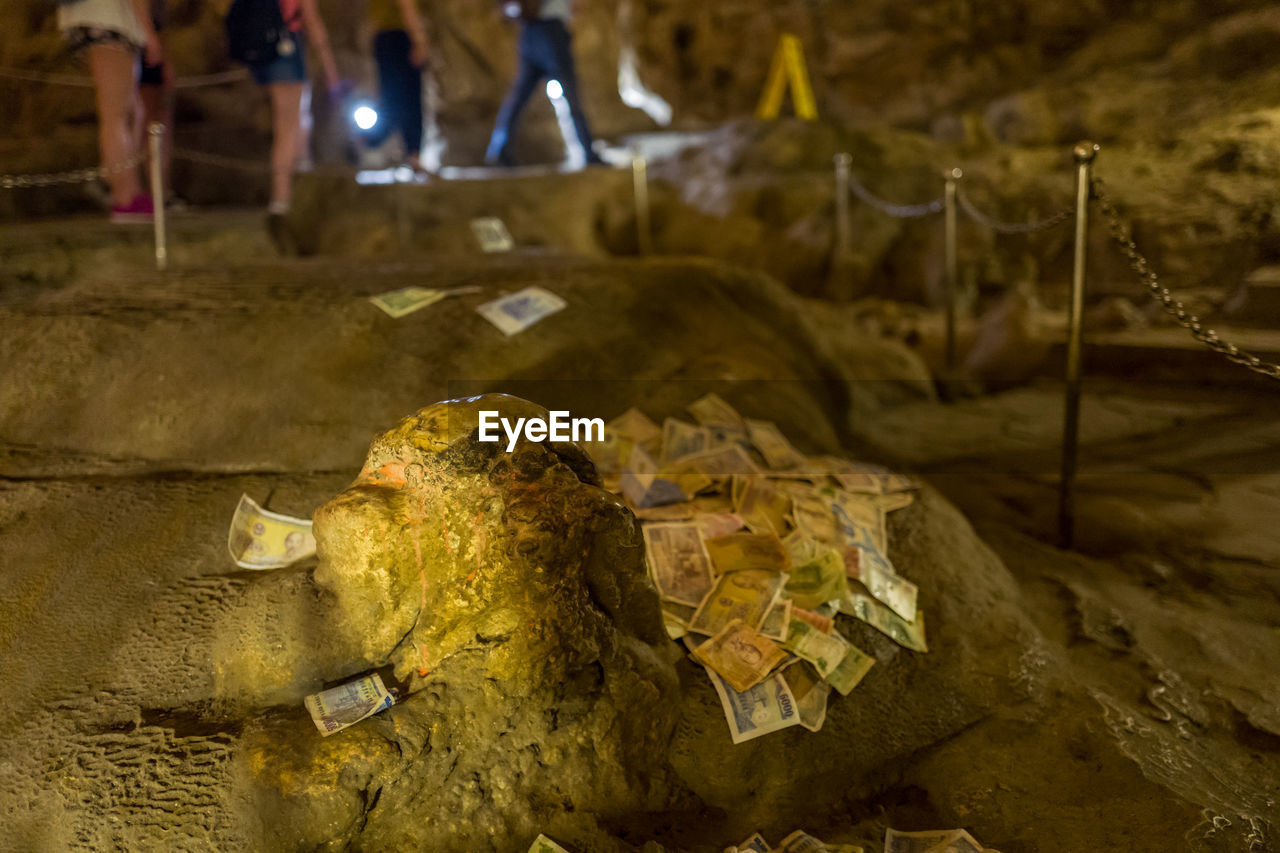 Paper currencies on rock in cave at halong bay