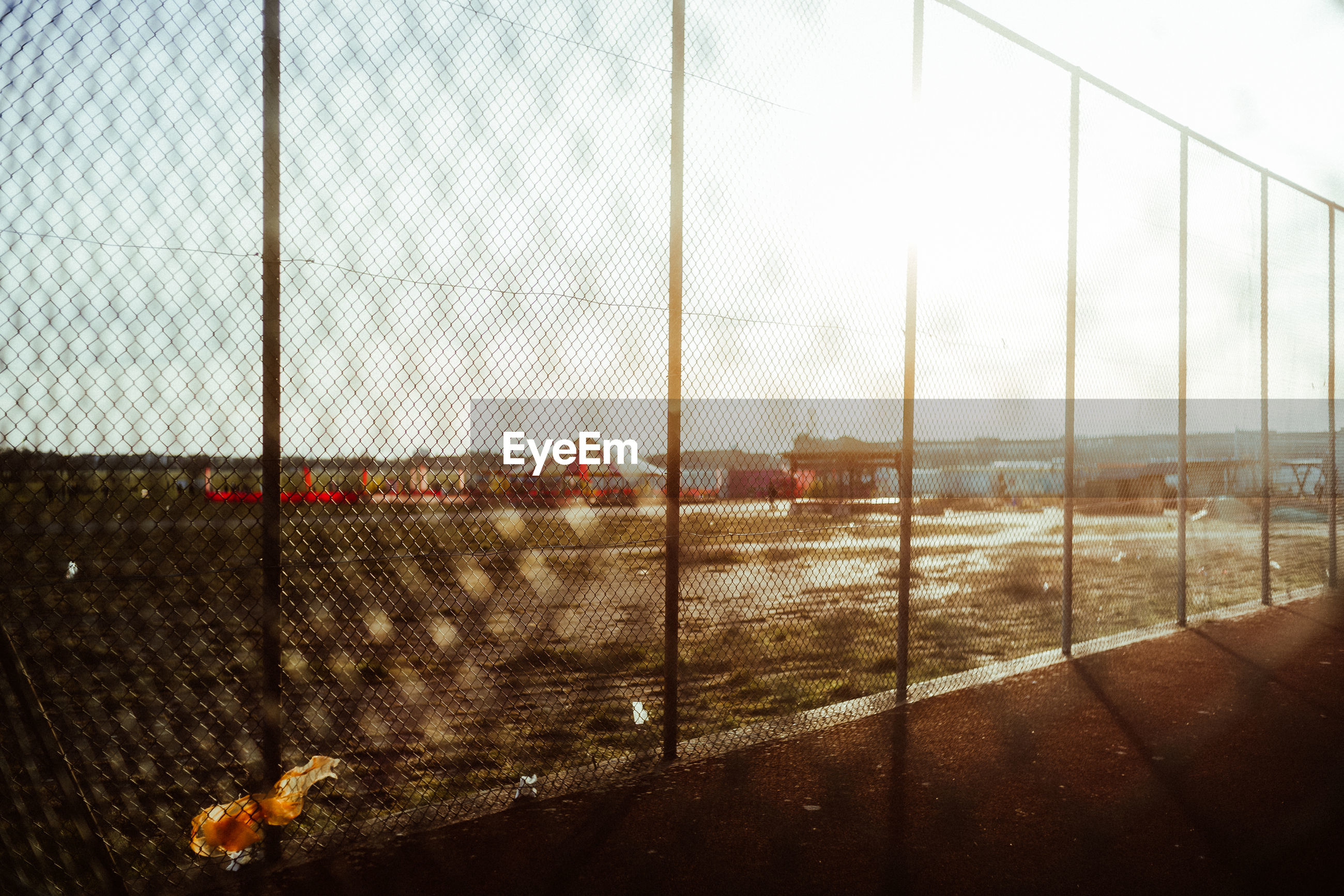 FENCE ON FIELD AGAINST SKY SEEN THROUGH CHAINLINK WINDOW
