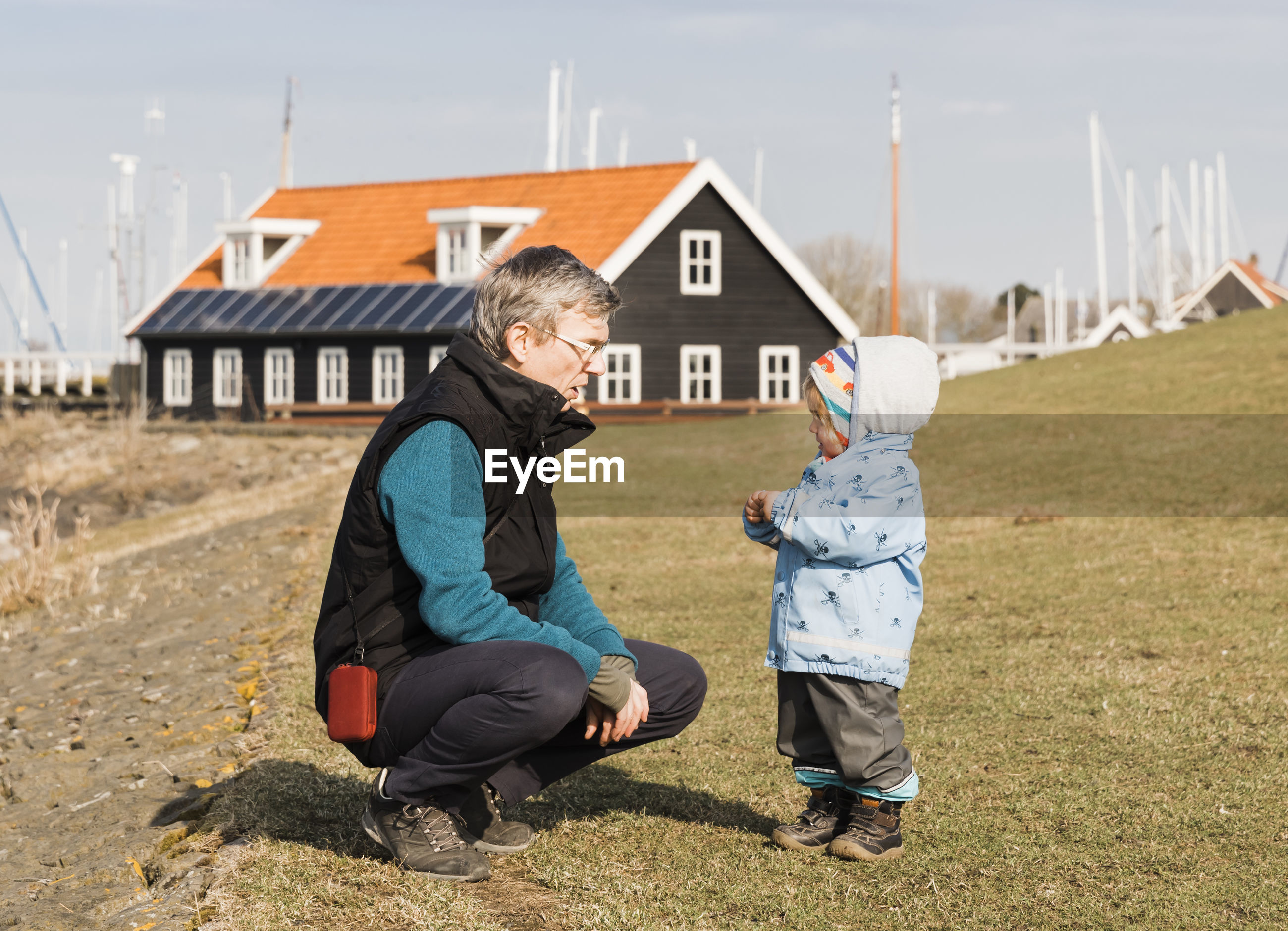 Grandfather with granddaughter crouching on field against house