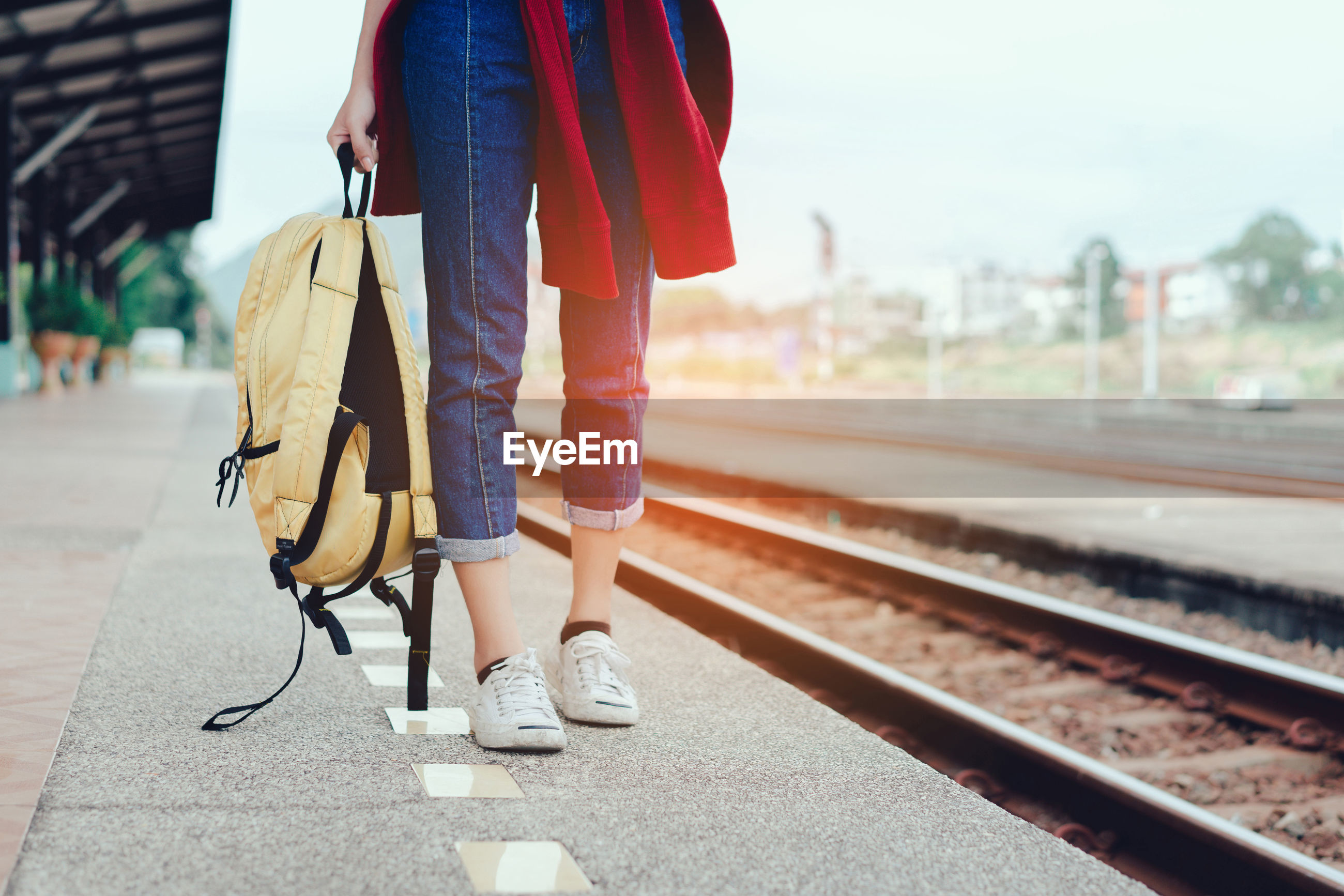 Low section of young woman holding backpack standing on railroad station