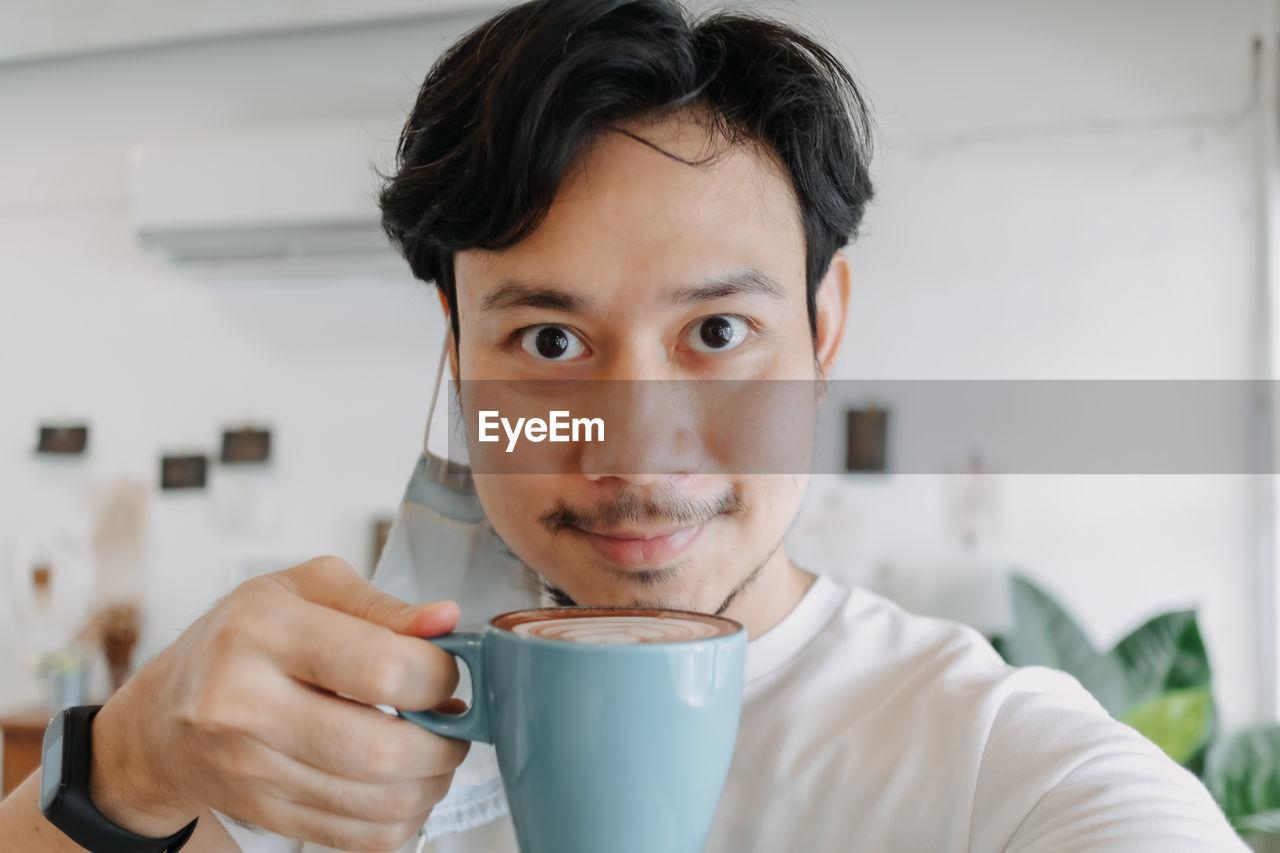 PORTRAIT OF MATURE MAN DRINKING COFFEE