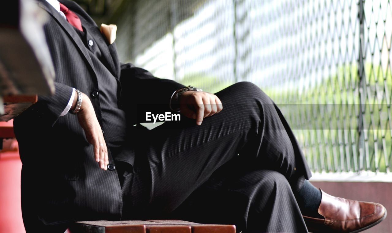 Low section of businessman sitting on bench