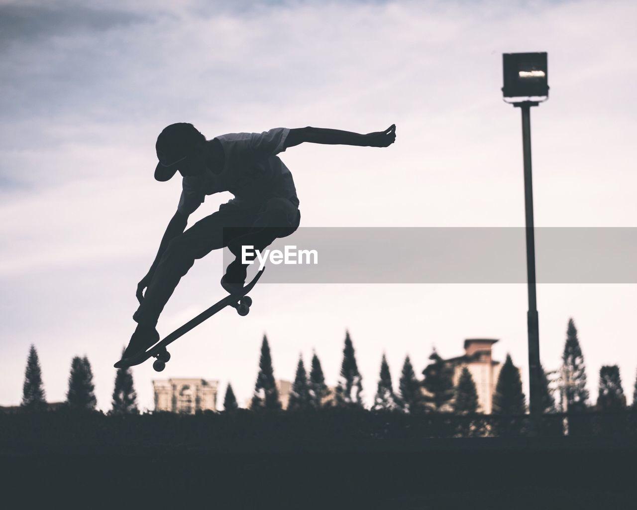 Skateboarder Performing Stunt Against Sky