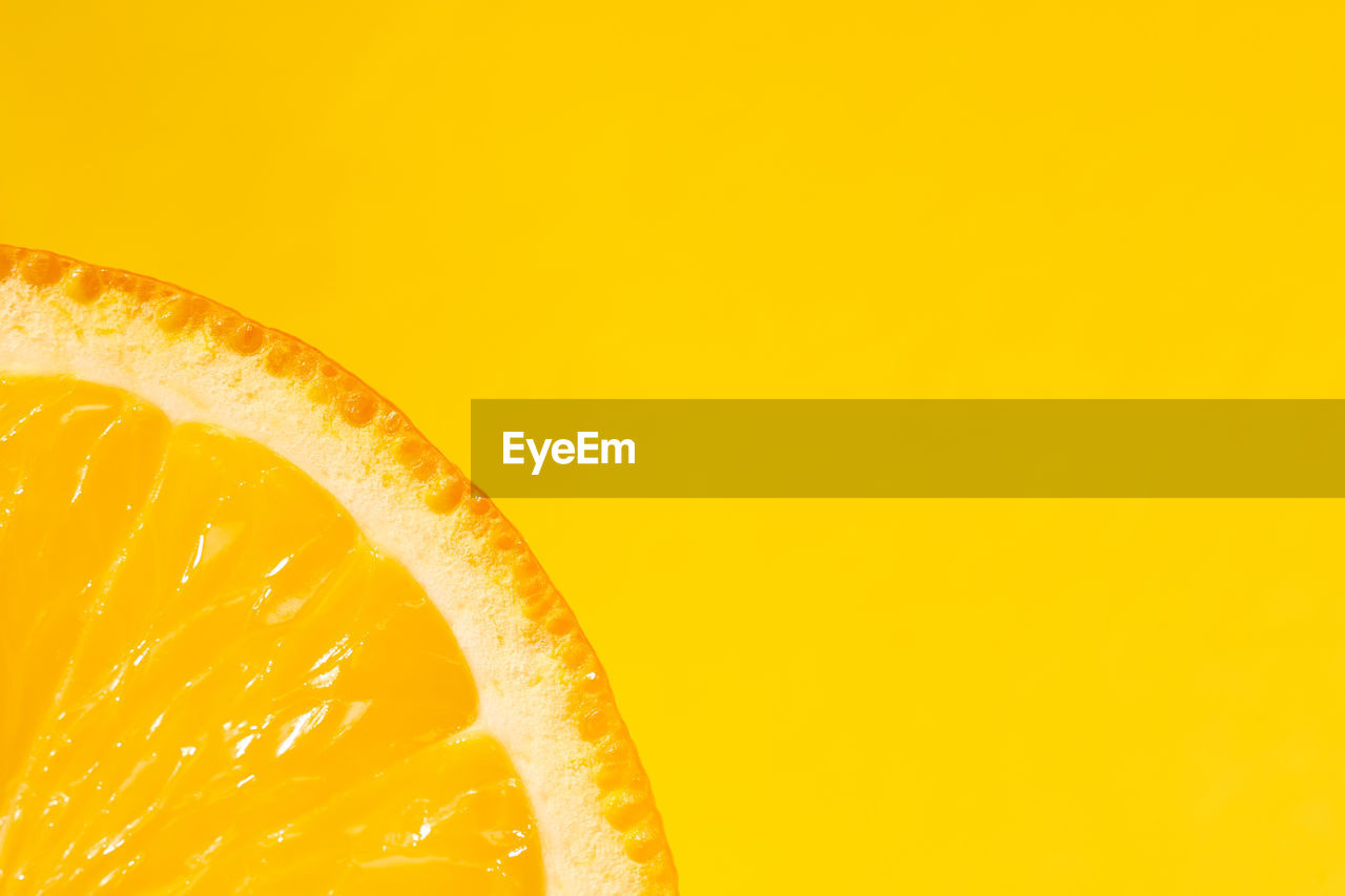 Sliced orange, yellow background, copy space. fresh juicy fruit, source of vitamin c. bright