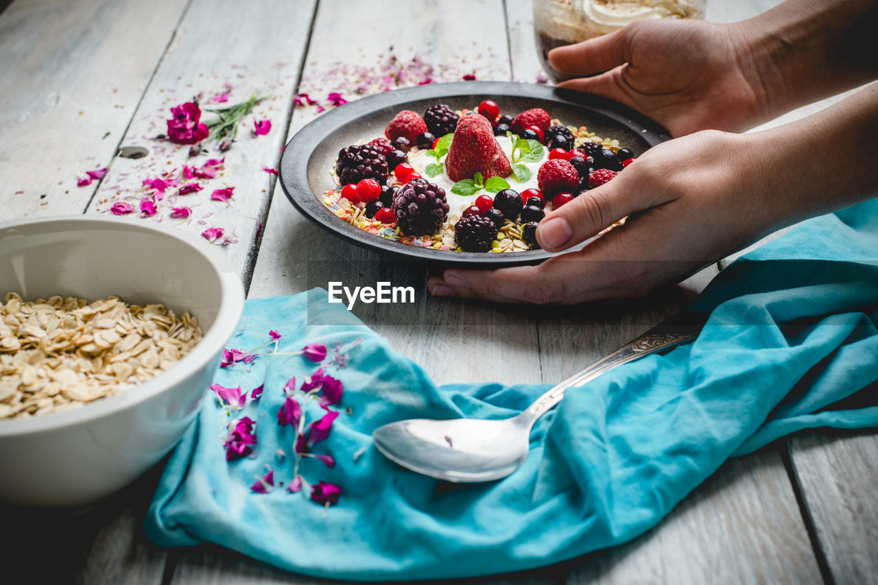 food, food and drink, bowl, wellbeing, healthy eating, human hand, one person, human body part, real people, freshness, table, hand, holding, lifestyles, indoors, high angle view, adult, fruit, berry fruit, meal, breakfast, finger