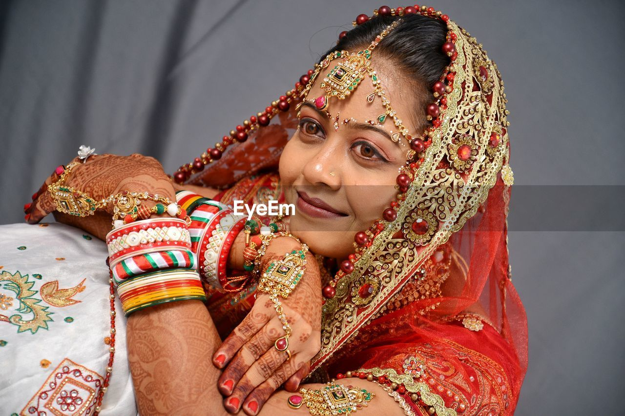 traditional clothing, one person, indoors, real people, newlywed, women, young adult, front view, young women, bride, henna tattoo, lifestyles, sari, clothing, sitting, adult, smiling, beautiful woman, wedding ceremony