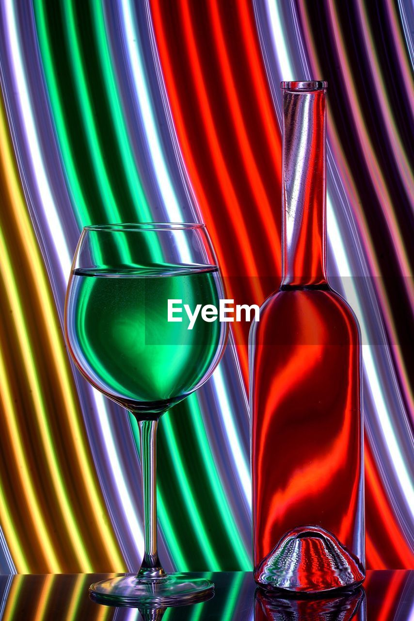 Glass Wine And Bottle Against Neon Background