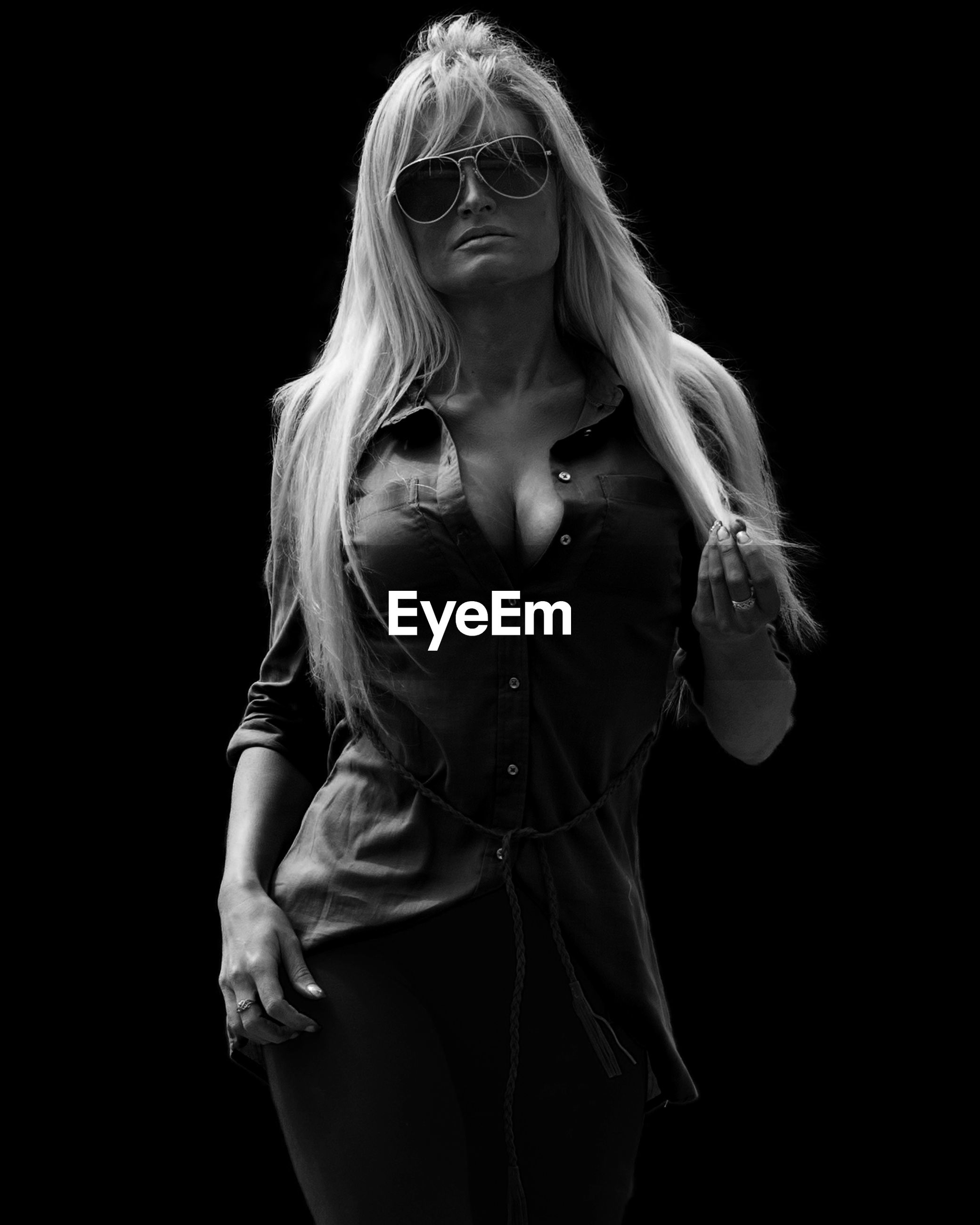 Portrait of young woman wearing sunglasses while standing against black background