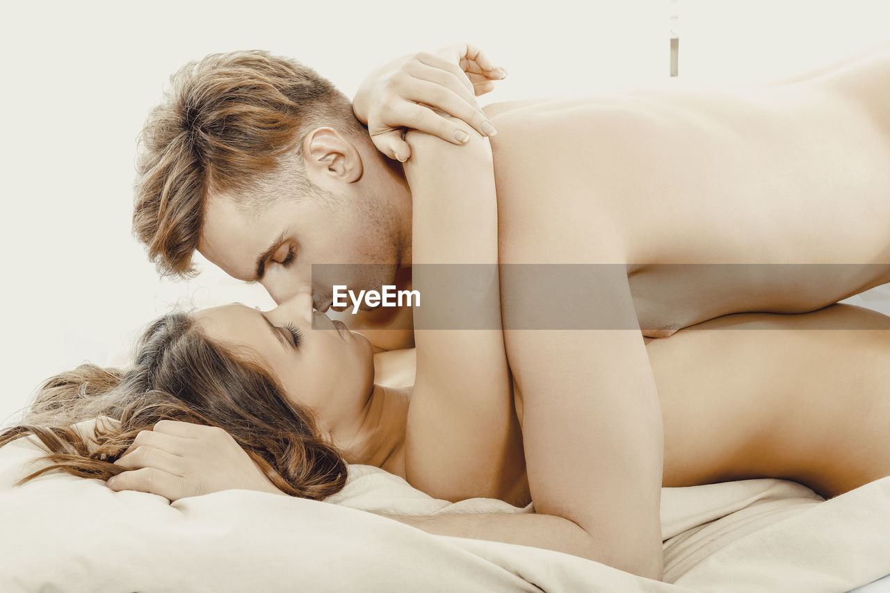 Naked Young Couple Romancing On Bed Against White Background