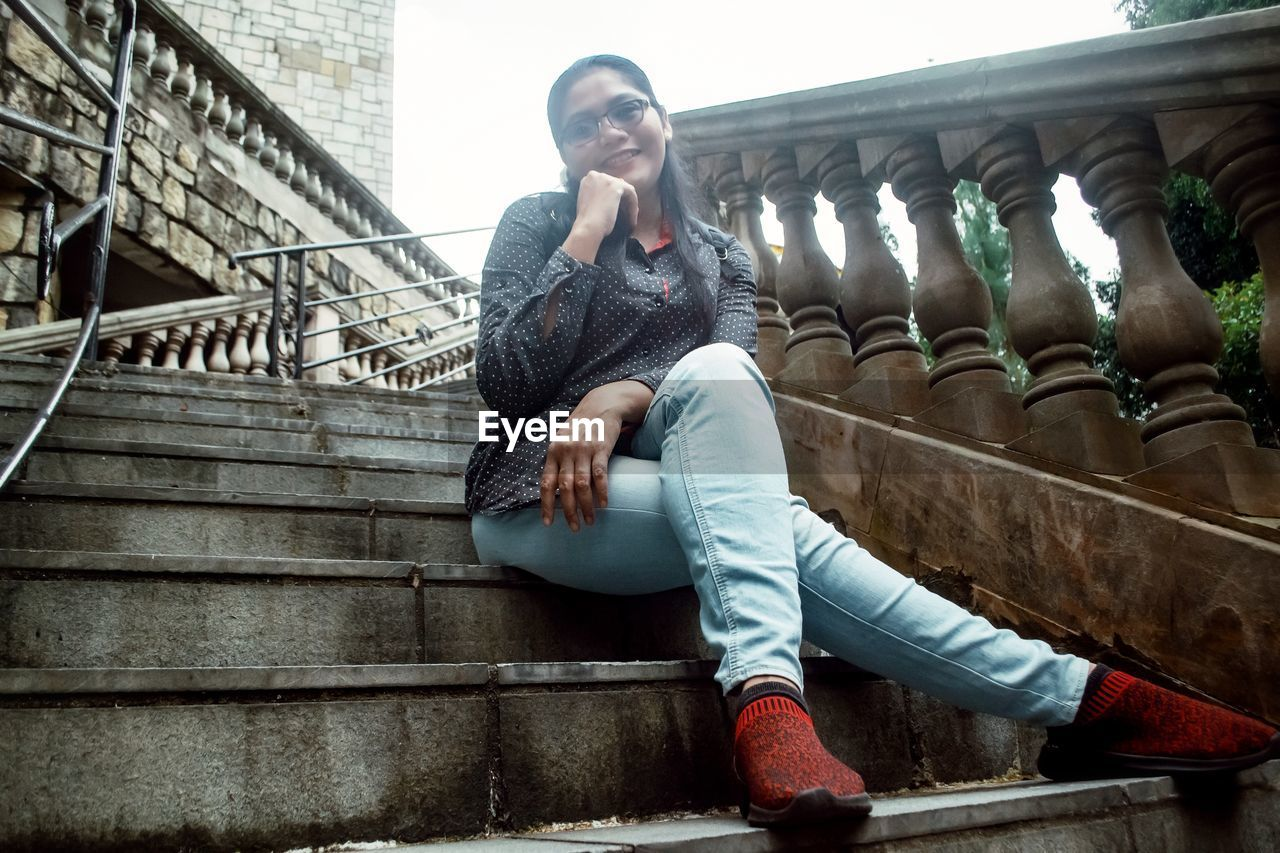 staircase, architecture, young adult, sitting, real people, full length, one person, young women, casual clothing, built structure, lifestyles, front view, steps and staircases, clothing, leisure activity, railing, building exterior, day, looking away, contemplation, hairstyle, outdoors, warm clothing, beautiful woman
