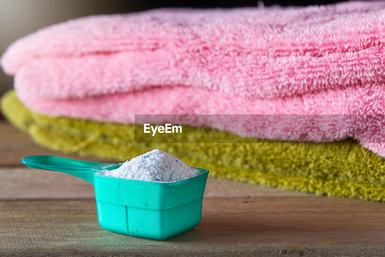 Close-up of laundry detergent in measuring cup against towels on table