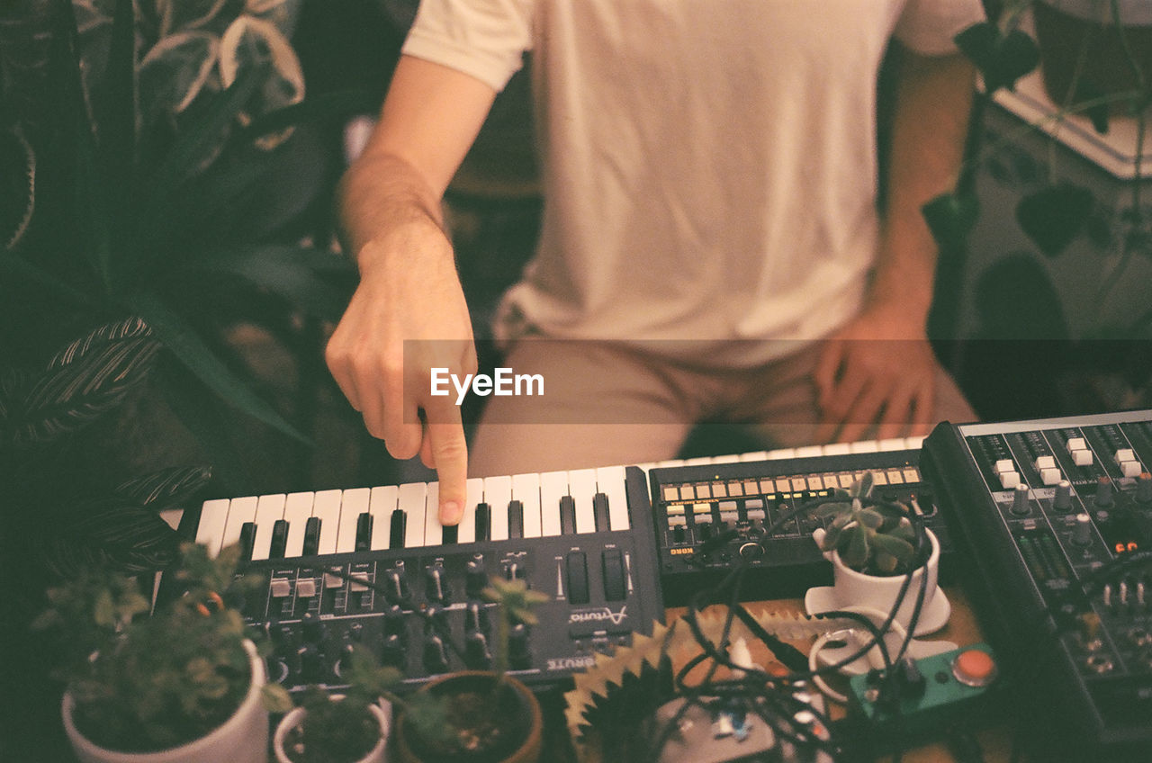 music, midsection, one person, technology, real people, men, musical instrument, artist, musician, sound mixer, occupation, musical equipment, indoors, sound recording equipment, arts culture and entertainment, audio equipment, dj, club dj, standing, mixing
