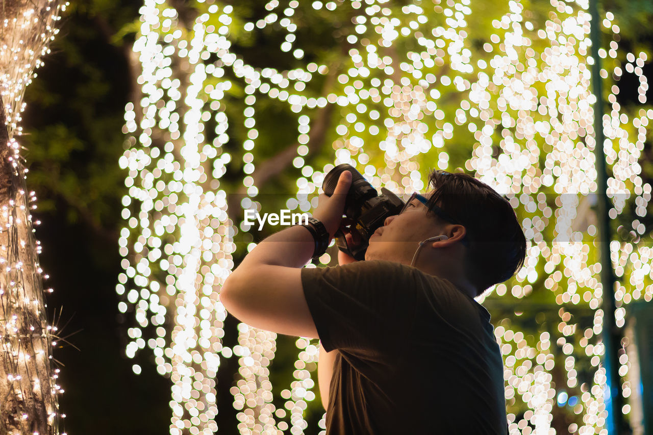 Man Photographing Through Camera Against Illuminated Lights At Night