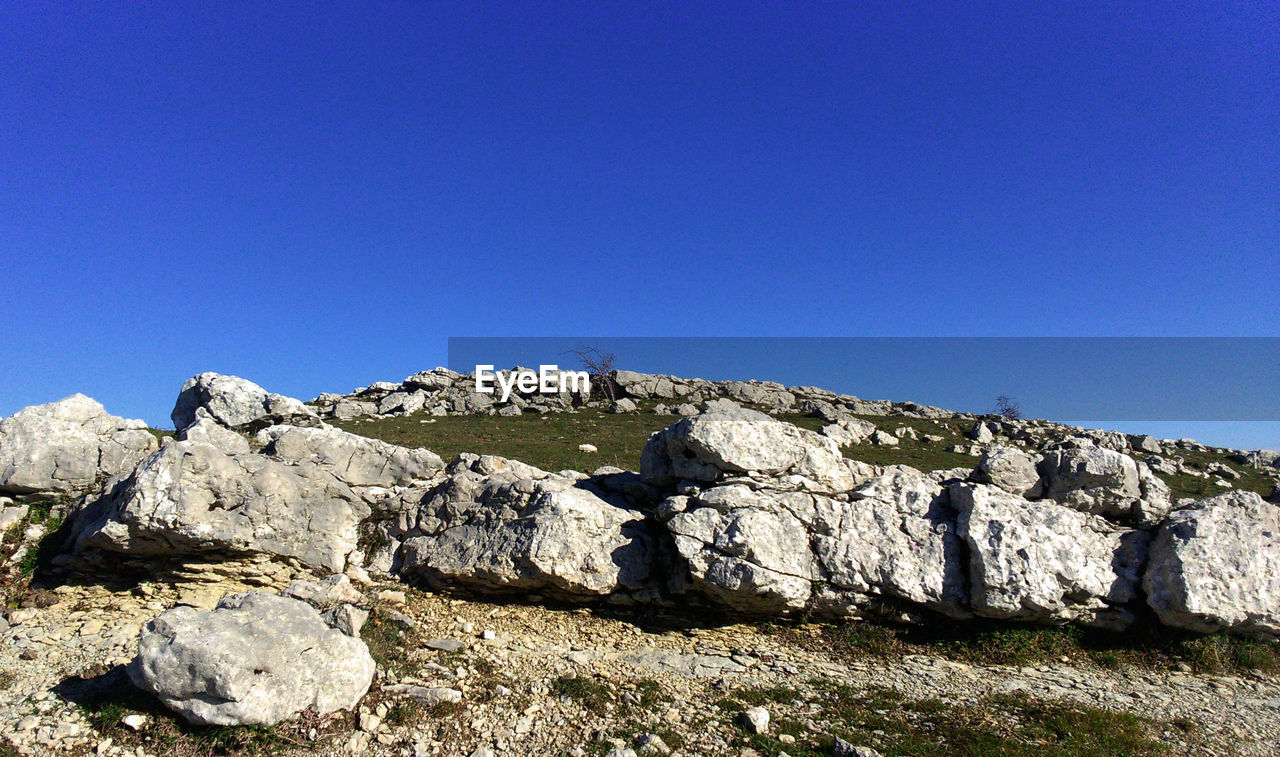 copy space, clear sky, blue, rock - object, no people, day, low angle view, outdoors, mountain, nature, sunlight, beauty in nature, sky