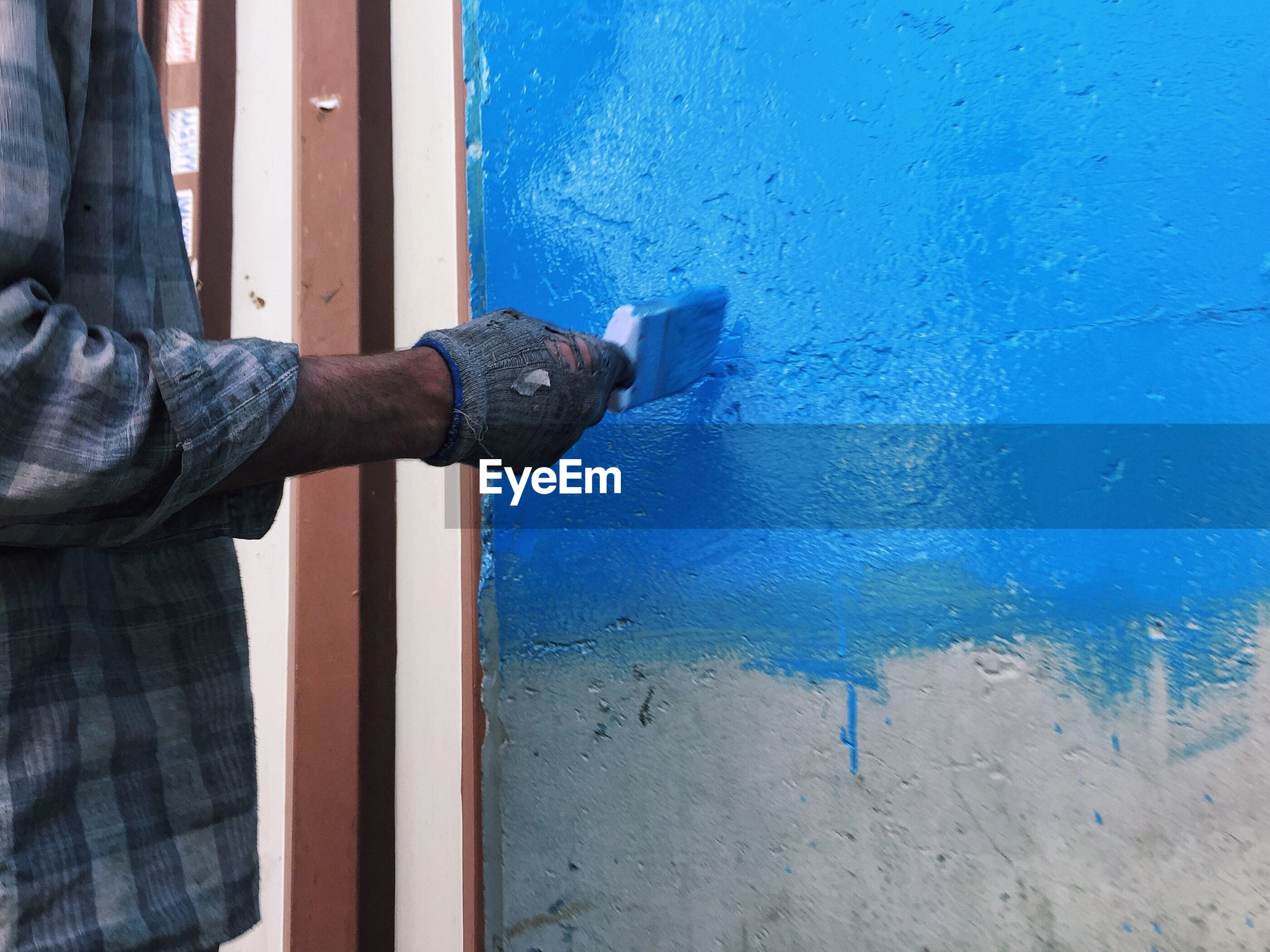 CLOSE-UP OF HUMAN HAND ON BLUE DOOR