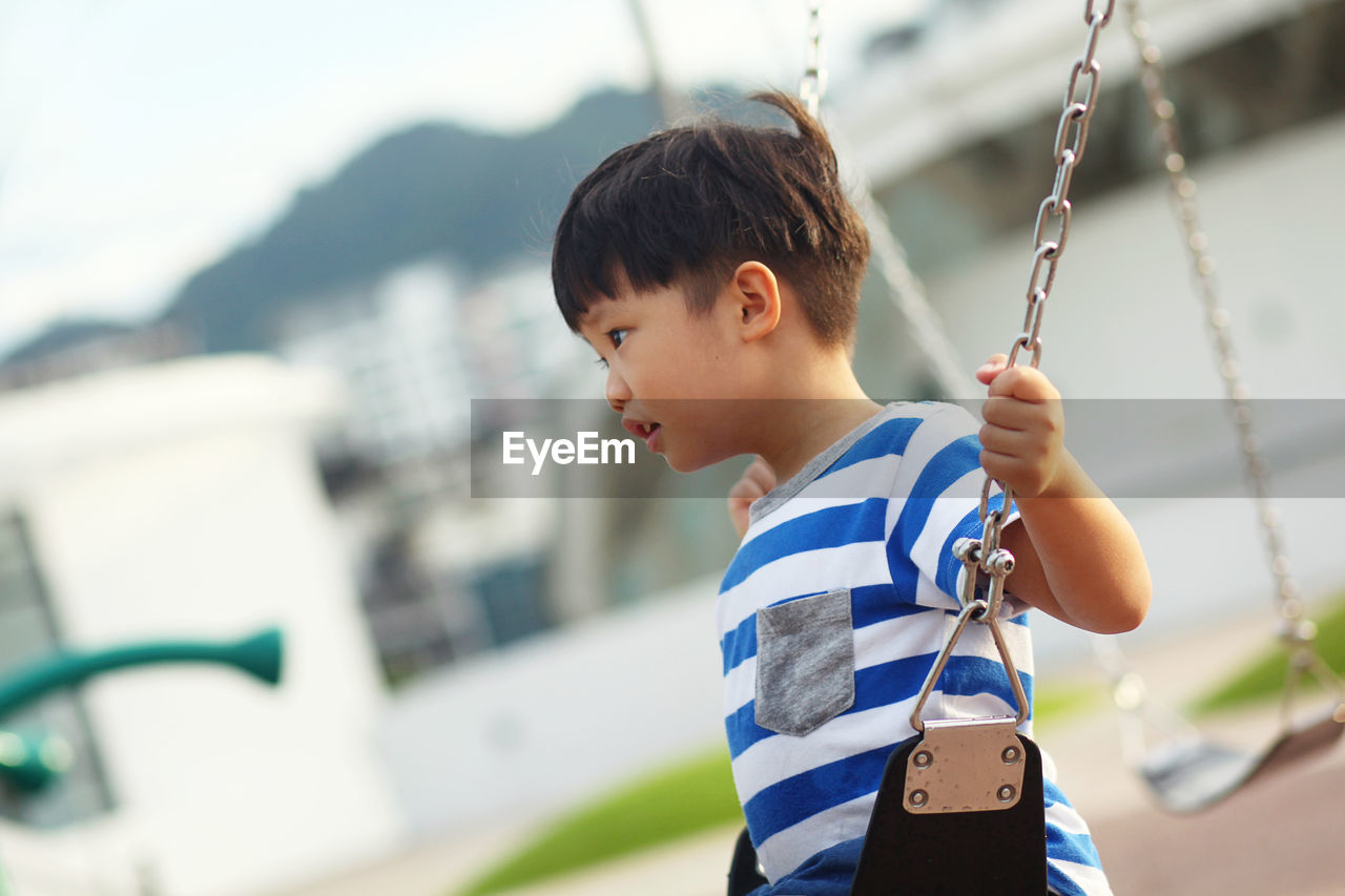 Side View Of Boy Swinging At Playground